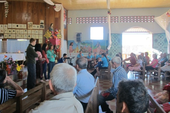 James and group speaking at Mass at Arcatao.  Sarah, group leader, has the microphone.