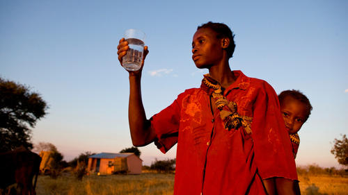 Winfreda Malilave holding a glass of clean water from the CAFOD-funded borehole.