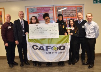 Headteacher Mr Hubbard, School Chaplain Mr Griffin, and Corpus Christi pupils, present the cheque to CAFOD